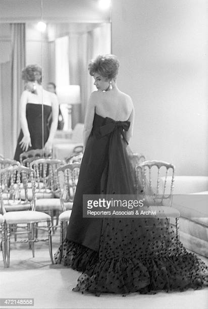 'Croatian actress Sylva Koscina trying on an evening dress in front of the mirror at Italian tailor Roberto Capucci's atelier Paris 1962 '