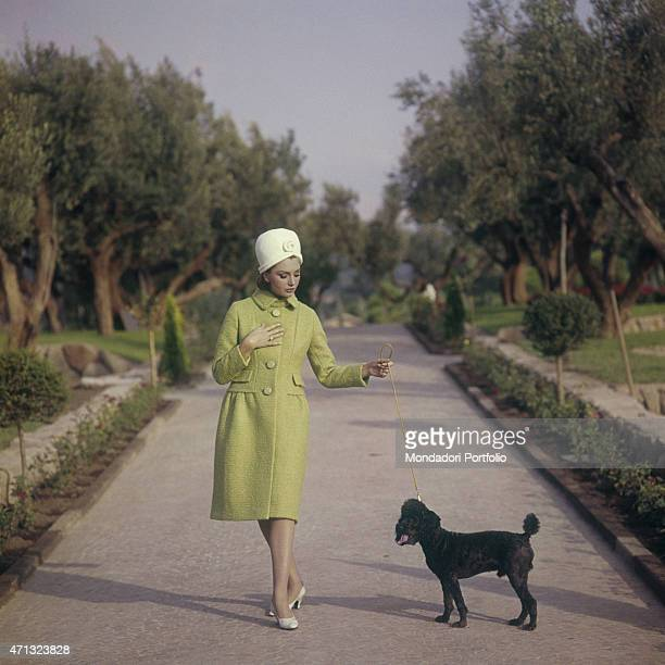 Croatian actress Sylva Koscina walking with a dog She wears an elegant green overcoat and a white turban hat 1964