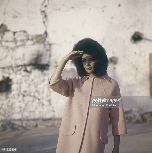 Croatian actress Sylva Koscina wearing a pale pink overcoat and a fur hat 1964