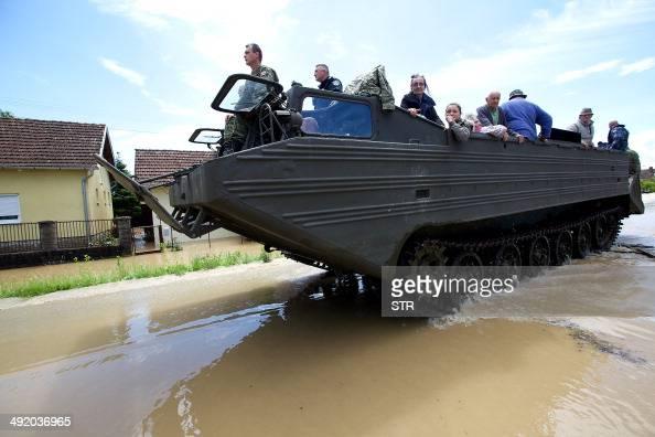 Croatian Army soldiers evacuate people in amphibian vehicle from their houses flooded in the village of Gunja in eastern Croatia 18 May 2014...