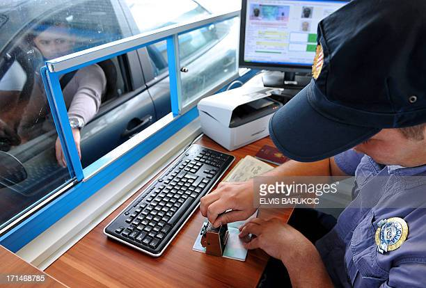 Croatian border police officer stamps a tourist's passport at the border between Croatia and Montenegro close to the Croatian village of Karasovici...