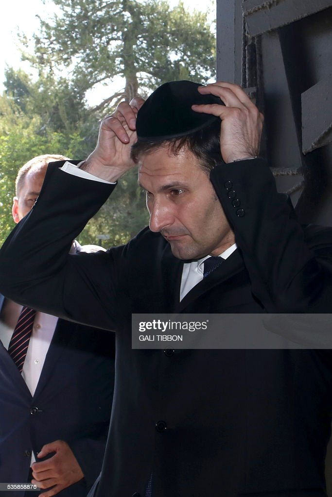 Croatian Foreign Minister Miro Kovac puts on a kippa, the traditional Jewish skullcap for men, on May 30, 2016 during his visit to the Yad Vashem Holocaust Memorial museum in Jerusalem commemorating the six million Jews killed by the Nazis during World War II. / AFP / GALI