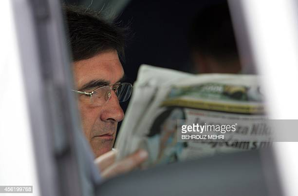 Croatian head coach of the Iranian team Branko Ivankovic reads a newspaper while leaves Krone hotel to fly to Leipzig for Iran's last match against...