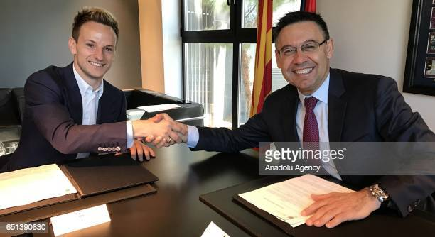 Croatian midfielder Ivan Rakitic shakes hands with FC Barcelona's president Josep Maria Bartomeu after he signed his new contract extension at Camp...