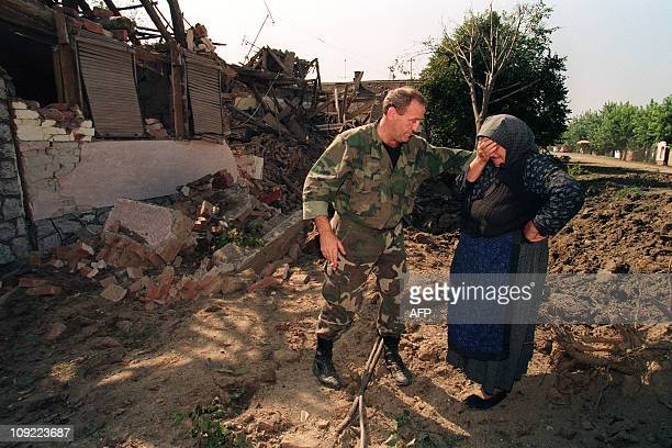 A Croatian National Guardsman comforts an old woman on September 26 outside her home which was destroyed in an air raid during the night by Yugoslav...