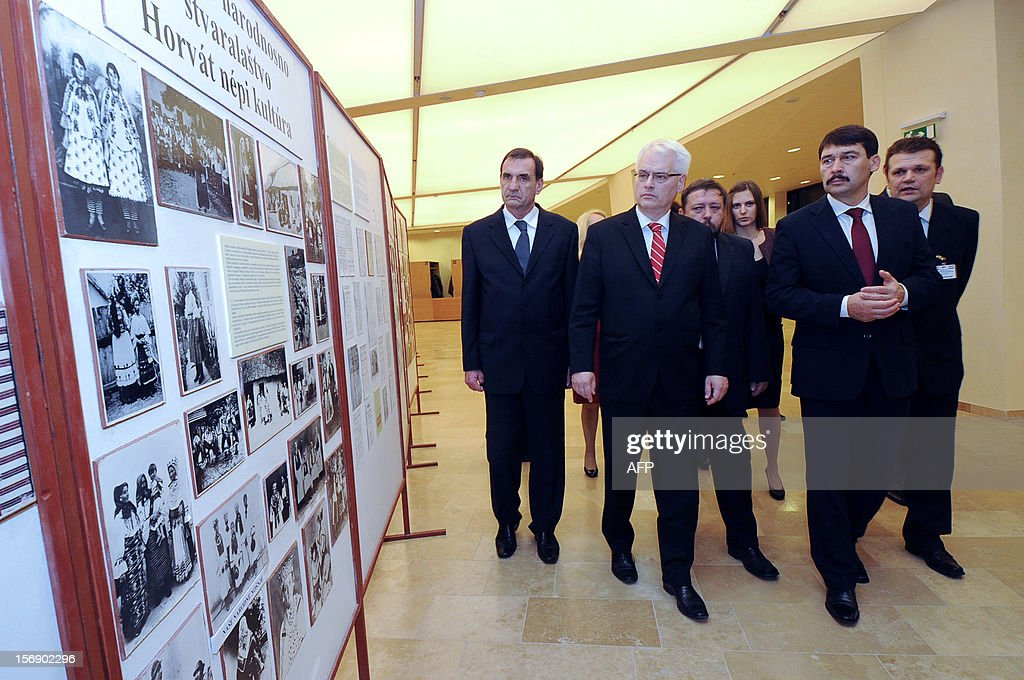 Croatian President Ivo Josipovic (C) and his Hungarian counterpart Janos Ader (2nd R) arrive for an exhibition after their joint press conference in the Kodaly cultural center of Pecs on November 24, 2012. Josipovic is a main guest of the Croatian Day in Hungary.