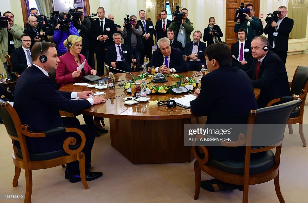 Croatian President Kolinda Grabar-Kitarovic (2nd L) and Presidents of the Visegrad countries (V4) Milos Zeman (C) of the Czech Republic, Andrej Kiska (R) of Slovakia and Janos Ader (2nd R) of Hungary discuss at the ball hall of the Anna Grand Hotel in Balatonfured on October 8, 2015 during their official meeting. The Polish President Andrzej Duda is expected to join the group later in the day.