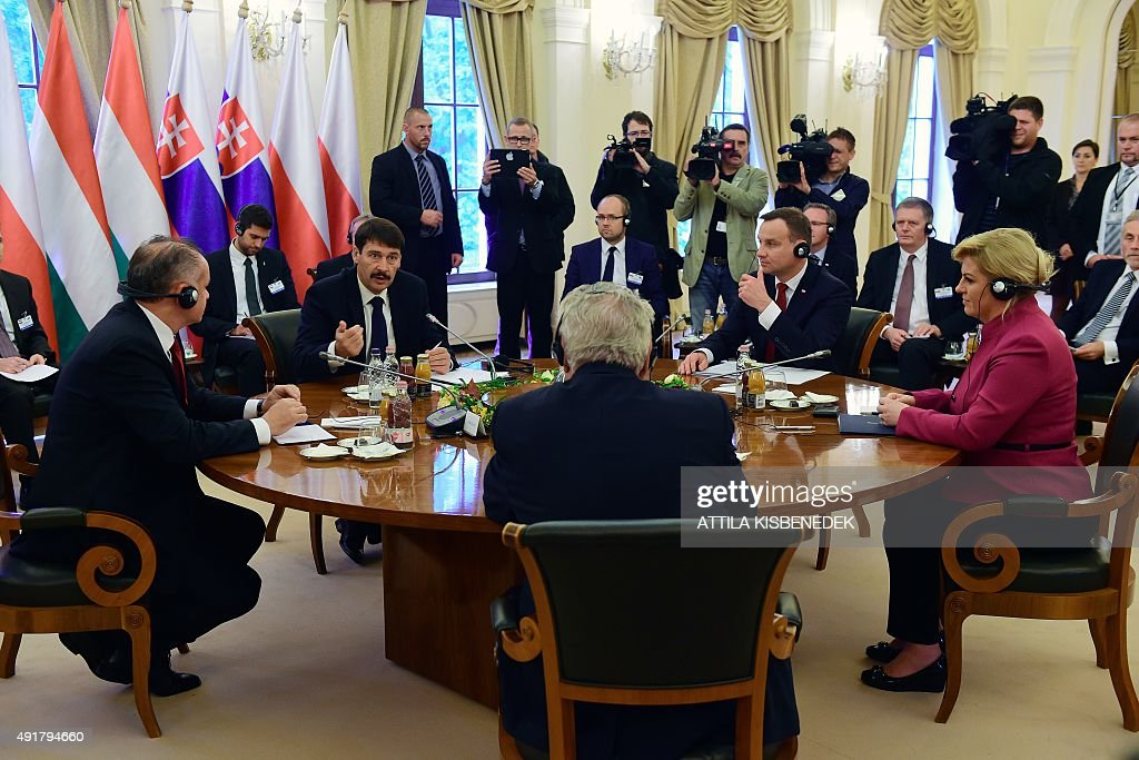 Croatian President Kolinda Grabar-Kitarovic (R) and Presidents of the Visegrad countries (V4) Milos Zeman (C, foreground) of the Czech Republic, Andrej Kiska (L) of Slovakia, Janos Ader (2nd L) of Hungary and Andrzej Duda (2nd R) of Poland discuss at the ball hall of the Anna Grand Hotel in Balatonfured on October 8, 2015 during their official meeting.