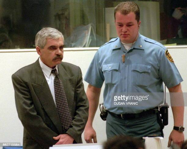 Croatian Serb Slavko Dokmanovic is flanked by a UN security guard 19 January as he stands trial before the United Nations War Crimes Tribunal for the...