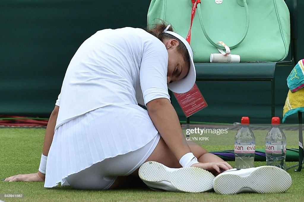 Croatia's Ana Konjuh lies on the court after stepping on the ball and injuring her ankle in a point against Poland's Agnieszka Radwanska during their women's singles second round match on the fourth day of the 2016 Wimbledon Championships at The All England Lawn Tennis Club in Wimbledon, southwest London, on June 30, 2016. / AFP / GLYN