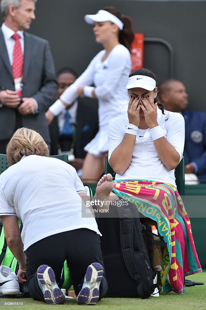 Croatia's Ana Konjuh receives treatment from the trainer after stepping on the ball and injuring her ankle in a point against Poland's Agnieszka Radwanska during their women's singles second round match on the fourth day of the 2016 Wimbledon Championships at The All England Lawn Tennis Club in Wimbledon, southwest London, on June 30, 2016. / AFP / GLYN