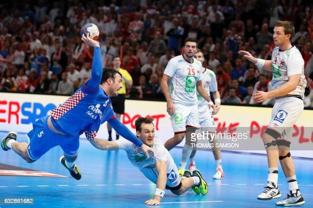 Croatia's centre back Domagoj Duvnjak jumps to shoot on goal despite Norway's centre back Christian O'Sullivan and Norway's centre back Sander...