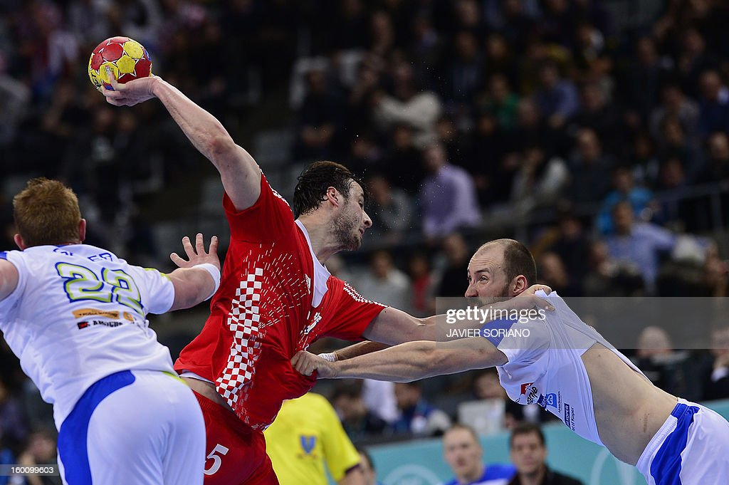 Croatia's centre back Domagoj Duvnjak (C) shoots past Slovenia's right wing Vid Kavticnik (R) during the 23rd Men's Handball World Championships bronze medal match Slovenia vs Croatia at the Palau Sant Jordi in Barcelona on January 26, 2013.