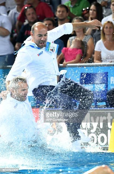 Croatia's coach Ivica Tucak jumps into the water as he celebrates the victory over Hungary with his team members in 'Hajos Alfred' swimming pool of...