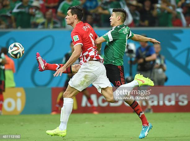 Croatia's defender Dejan Lovren and Mexico's forward Oribe Peralta vie for the ball during a Group A football match between Croatia and Mexico at the...