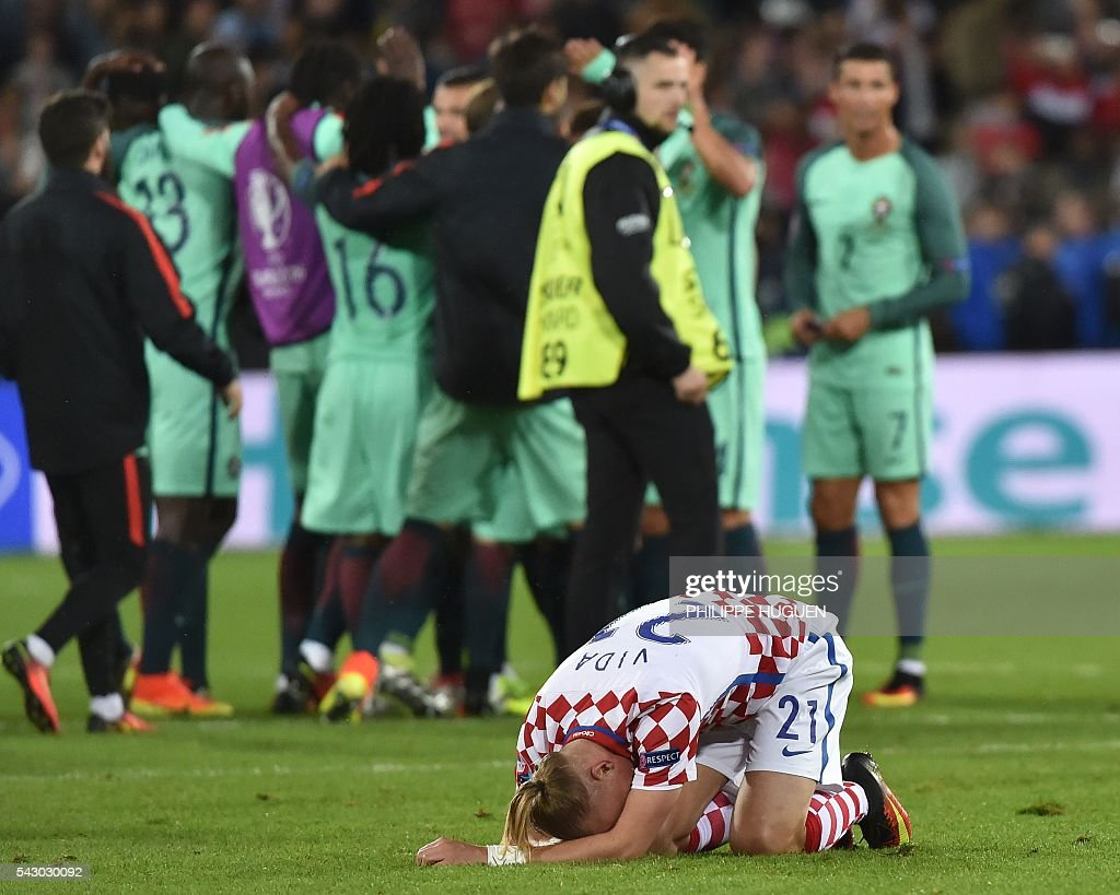 Croatia's defender Domagoj Vida bends on the pitch as Portugal's players celebrate at the end of the Euro 2016 round of sixteen football match Croatia vs Portugal, on June 25, 2016 at the Bollaert-Delelis stadium in Lens. / AFP / PHILIPPE