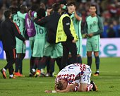 Croatia's defender Domagoj Vida bends on the pitch as Portugal's players celebrate at the end of the Euro 2016 round of sixteen football match...