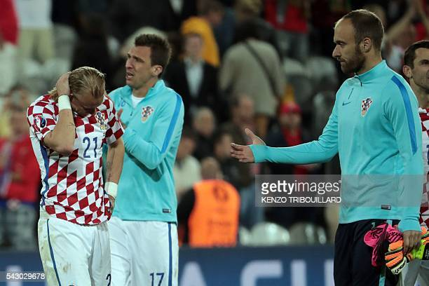 Croatia's goalkeeper Ivan Vargic conforts Croatia's defender Domagoj Vida after the round of sixteen football match Croatia against Portugal of the...