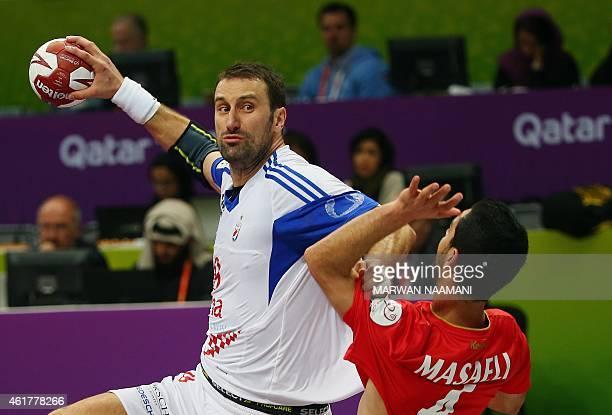 Croatia's Igor Vori attempts a shot on goal over Iran's Milad Masaeli during the 24th Men's Handball World Championships preliminary round Group B...
