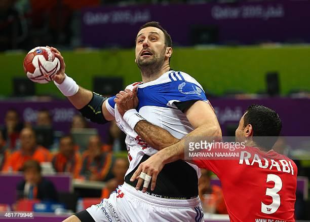Croatia's Igor Vori attempts a shot on goal over Iran's Mohammadreza Rajabi during the 24th Men's Handball World Championships preliminary round...