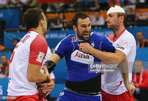 Croatia's Igor Vori tries to get past Polish defenses during the 24th Men's Handball World Championships quarterfinals match between Poland and...