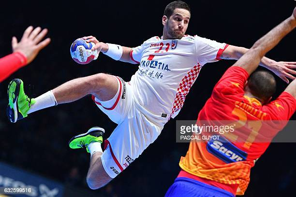 TOPSHOT Croatia's left back Stipe Mandalinic attempts a shot on goal over Spain's left back Joan Canellas during the 25th IHF Men's World...