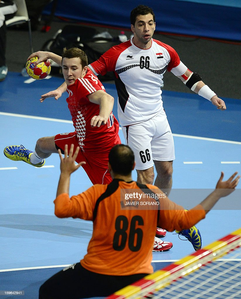 Croatia's left wing Manuel Strlek (L) shoots as he vies with Egypt's right back Ahmed Mostafa (R) and Egypt's goalkeeper Hady Mohamed (86) during the 23rd Men's Handball World Championships preliminary round Group D match Croatia vs Egypt at the Caja Magica in Madrid on January 17, 2013. AFP PHOTO/ JAVIER SORIANO