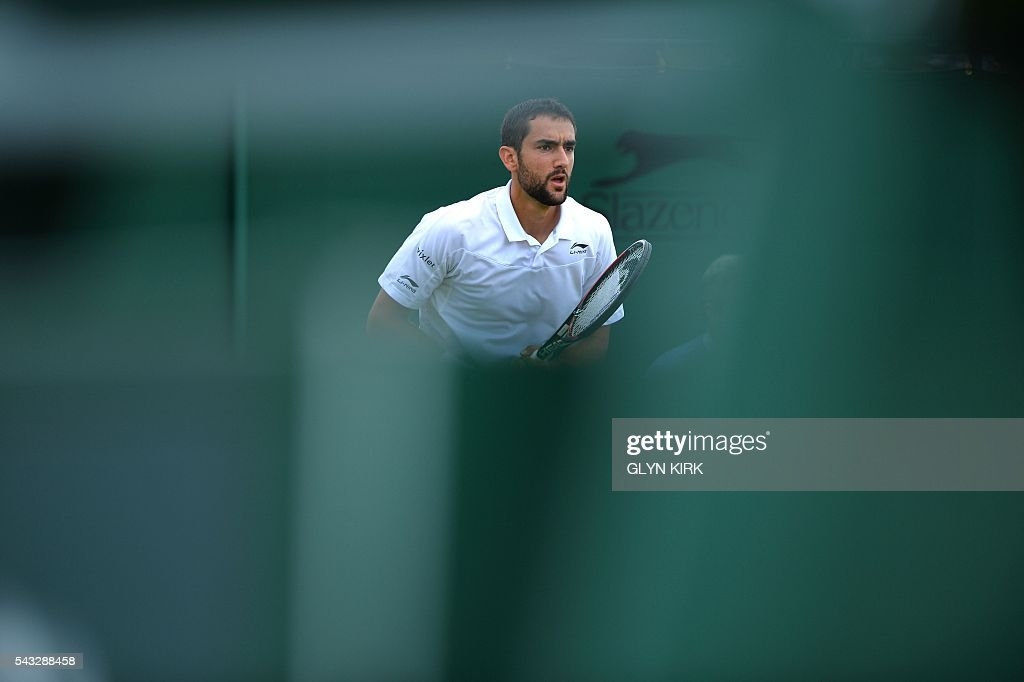 Croatia's Marin Cilic plays against US player Brian Baker during their men's singles first round match on the first day of the 2016 Wimbledon Championships at The All England Lawn Tennis Club in Wimbledon, southwest London, on June 27, 2016. / AFP / GLYN