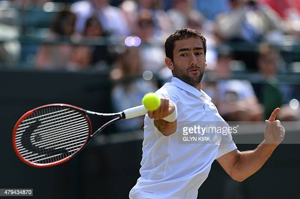 Croatia's Marin Cilic returns against US player John Isner during their men's singles third round match on day six of the 2015 Wimbledon...
