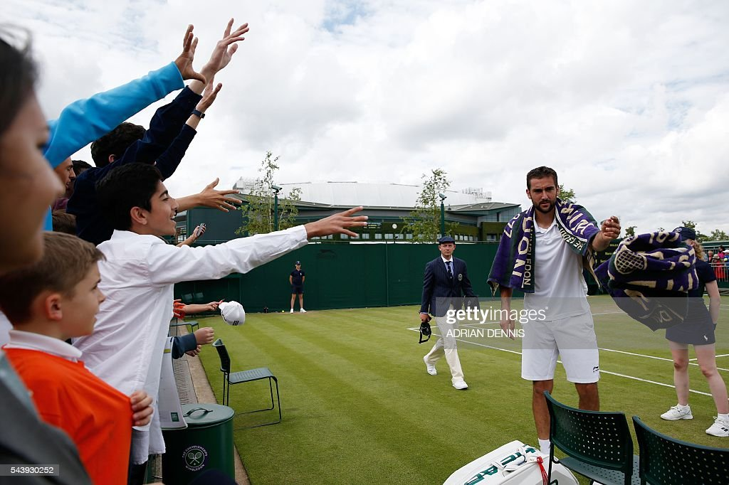 Croatia's Marin Cilic (R) throws a towel after beating Ukraine's Sergiy Stakhovsky during their men's singles second round match on the fourth day of the 2016 Wimbledon Championships at The All England Lawn Tennis Club in Wimbledon, southwest London, on June 30, 2016. / AFP / ADRIAN