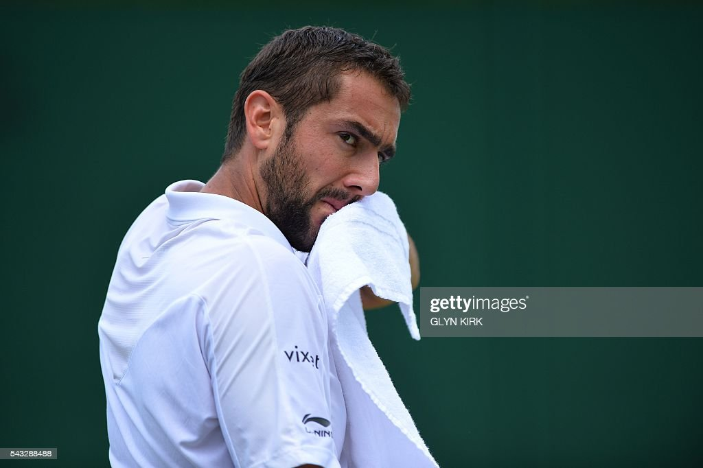 Croatia's Marin Cilic wipes his face between points against US player Brian Baker during their men's singles first round match on the first day of the 2016 Wimbledon Championships at The All England Lawn Tennis Club in Wimbledon, southwest London, on June 27, 2016. / AFP / GLYN