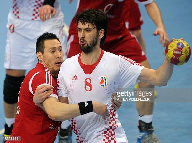 Croatia's Marko Kopljar is fouled by Hungary's Istvan Schuch during the men's European Handball Championships qualification match of Hungary vs...