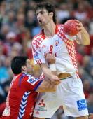Croatia's Marko Kopljar vies with Serbia's Nenad Vuckovic during the men's EHF Euro 2012 Handball Championship semifinal match Serbia vs Croatia on...