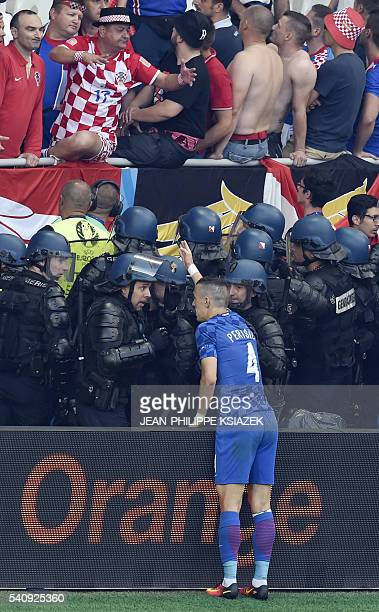 TOPSHOT Croatia's midfielder Ivan Perisic speaks to French riot police as flares are lobed onto the pitch during the Euro 2016 group D football match...