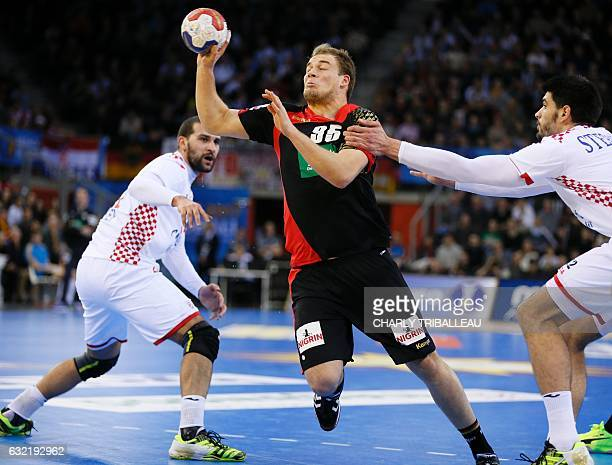 Croatia's right back Luka Stepancic holds back Germany's centre back Paul Drux during the 25th IHF Men's World Championship 2017 Group C handball...