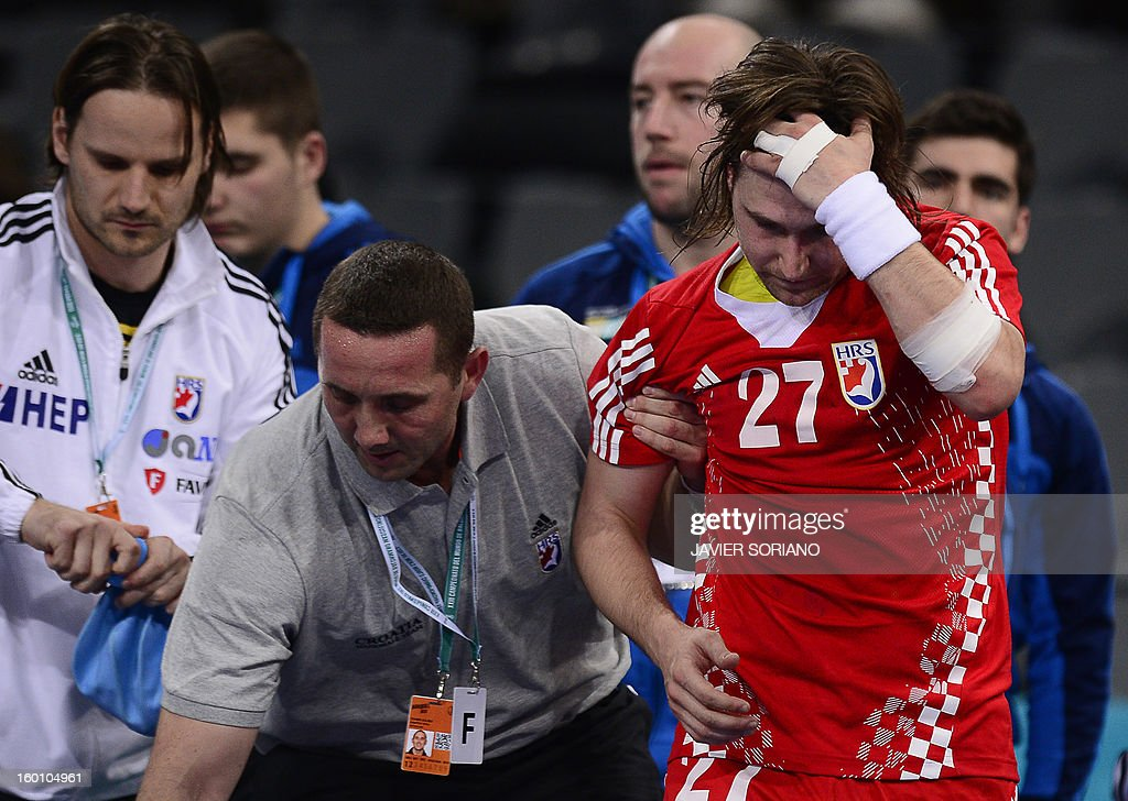 Croatia's right wing Ivan Cupic (R) is helped after being injured during the 23rd Men's Handball World Championships bronze medal match Slovenia vs Croatia at the Palau Sant Jordi in Barcelona on January 26, 2013. AFP PHOTO/ JAVIER SORIANO