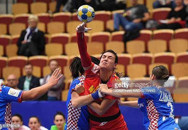 Croatia's Vesna Milanovic Litre and Nikolina Zadravec vie with Romania's Cristina Neagu during the Women's European Handball Championship Group D...