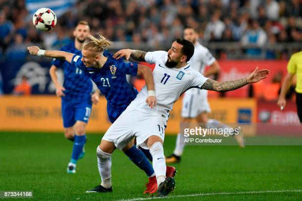 Croatria's Domagoj Vida vies with Greece's Konstantinos Mitroglou during the World Cup 2018 playoff football match Greece vs Croatia on November 12...