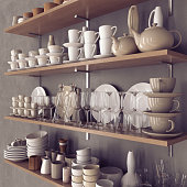 Simple crockery at wood shelves on concrete wall. Three-quarter view.