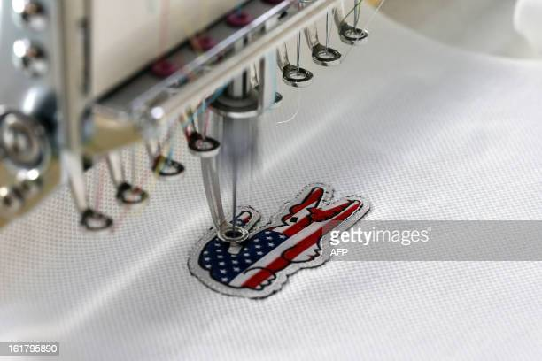 A crocodile the Lacoste logo bearing colors of the US flag is being stitched on a polo on January 7 2013 at a Lacoste plant in Troyes Lacoste polo...