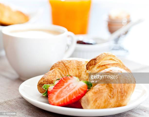 Croissant and sliced strawberry on a plate in front of mug
