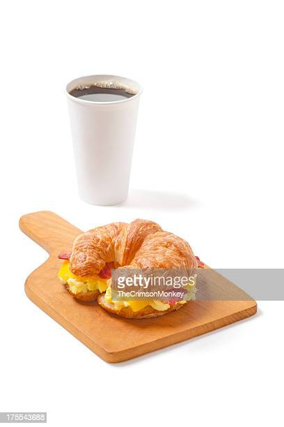 Croissant un sándwich de desayuno con huevos, queso y tocino y café