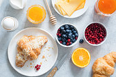 Continental breakfast table top view. Fresh croissants, boiled egg, cheese, orange, jam, honey, blueberries and currants on bright blue table. Horizontal