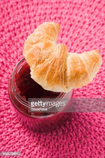 Croissant on a jar of raspberry jam (overhead view)
