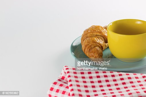 croissant on green dish with yellow cup coffee. : Stock Photo