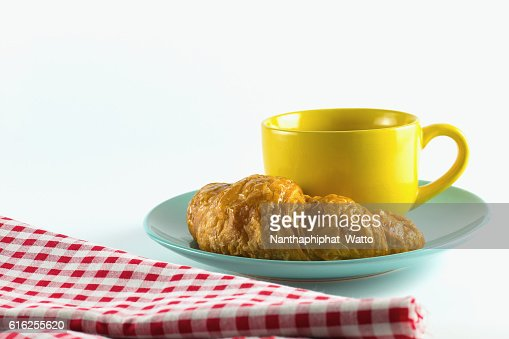 croissant on green dish with yellow cup coffee. : Foto de stock