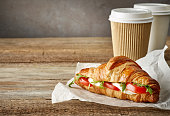 croissant sandwich with tomato and mozzarella on wooden table