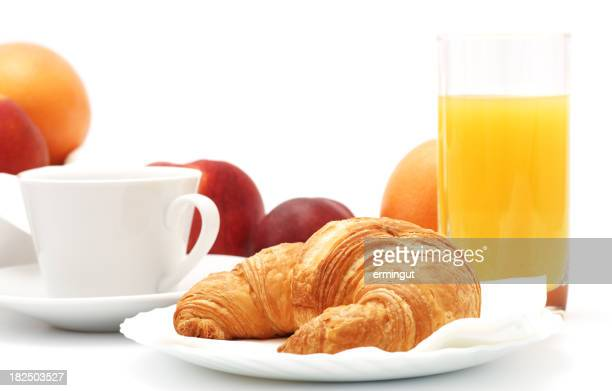 Croissant with coffee, fruit and juice on plate