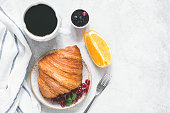 Continental breakfast with fresh croissant, berries, jam, black coffee and orange wedge on a table. Top view, copy space for your text