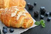 Croissant with fresh berries on black slate background